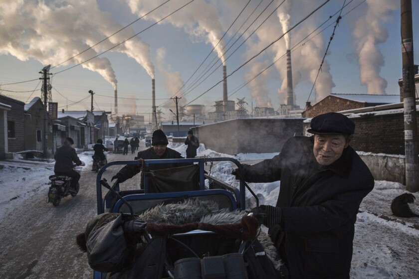 Smoke billows from stacks as men pull a tricycle in a neighborhood next to a coal-fired power plant in Shanxi, China.