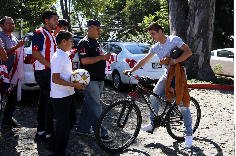 Isaac Brizuela (d) en su llegada a las instalaciones de Verde Valle a bordo de su bicicleta, mostrando su rechazo al gasolinazo.
