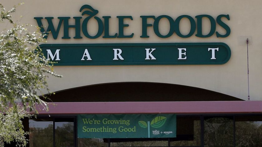 Shoppers come and go from Whole Foods Market grocery store, Monday, Aug. 28, 2017 in Chandler, Ariz.
