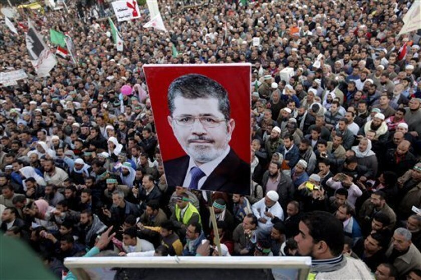 Thousands of Egyptian protesters shout slogans supporting Islamist President Mohammed Morsi, his poster at center, during a rally outside Cairo University in Cairo, Egypt, Friday, Feb. 15, 2013. Several thousand mostly hard-line Islamists protested in Cairo on Friday against a recent wave of violen
