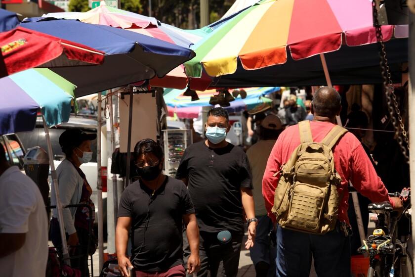 People, wearing masks against the coronavirus, shop along Alvarado Street in MacArthur Park in Los Angeles.