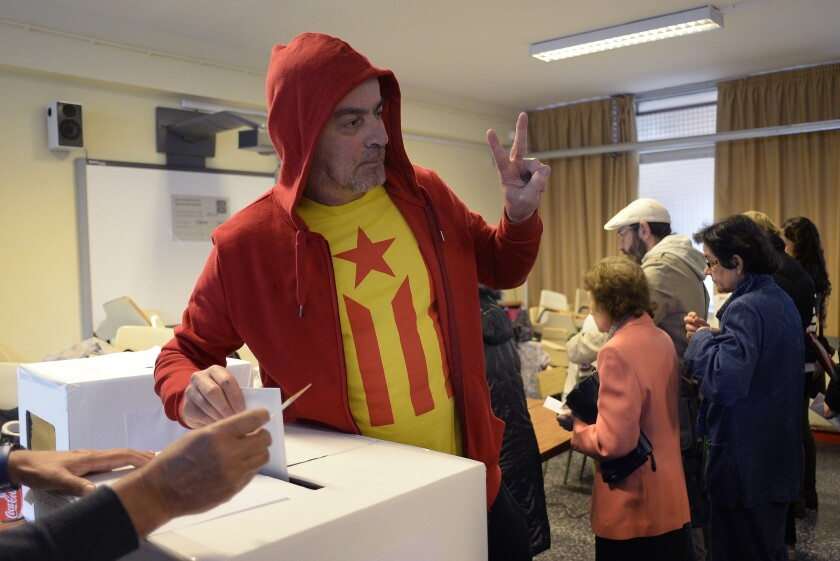 A man with a pro-independence Catalan flag on his T-shirt casts his vote in Barcelona on Sunday in an unofficial referendum asking whether the Catalonia region should break away from Spain.