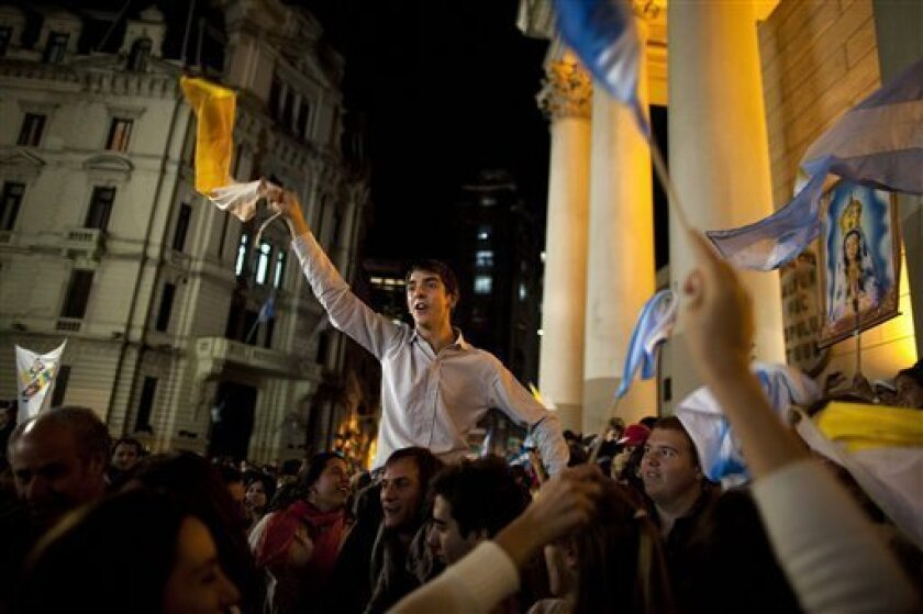 Faithful wave Vatican and Argentine flags as they sing outside the Metropolitan Cathedral in Buenos Aires, Argentina, Wednesday, March 13, 2013. Latin Americans reacted with joy on Wednesday at news that the Argentine Cardinal Jorge Mario Bergoglio was elected pope. Bergoglio, who chose the name Pope Francis, is the first pope ever from the Americas. (AP Photo/Ivan Fernandez)