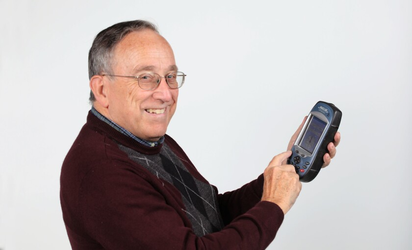 Philip de Barros, a professor of anthropology at Palomar College, holding a small GPS unit.