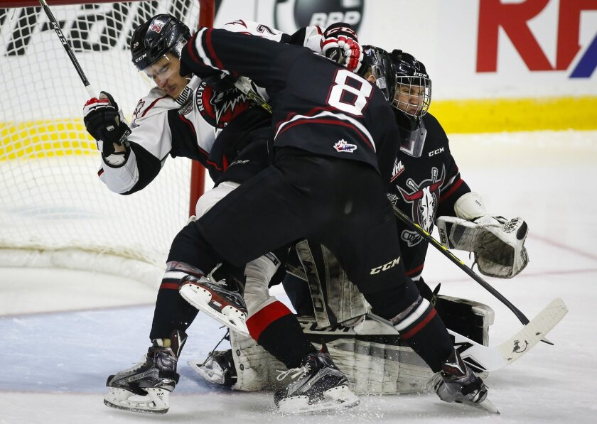 Rouyn-Noranda Huskies' Timo Meier, left, from Switzerland, is checked by Red Deer Rebels' Kayle Doetzel, center, as goalie Rylan Toth grimaces during the first period of a CHL Memorial Cup hockey game Friday, May 27, 2016, in Red Deer, Alberta. (Jeff McIntosh/The Canadian Press via AP)