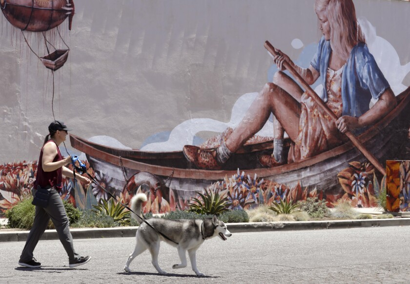 A woman and a dog walk past a mural of a girl rowing a boat