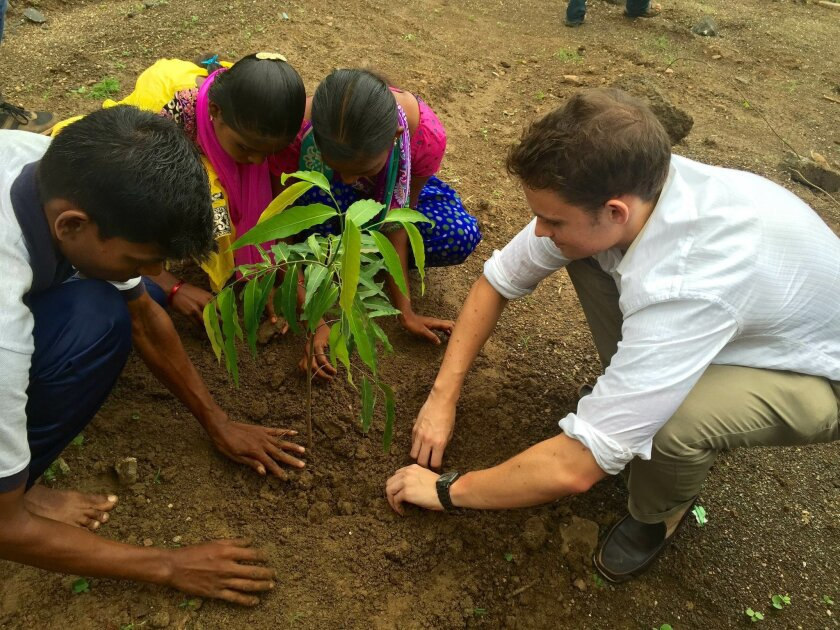 Kyle Joyner joins local students in planting a tree at their school to celebrate the high scores they earned on their Secondary School Board Exams. Courtesy photo