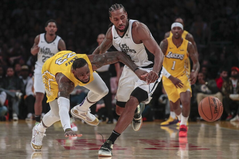 Clippers forward Kawhi Leonard knocks the ball from Lakers forward LeBron James during the fourth quarter of an NBA game Dec. 25.