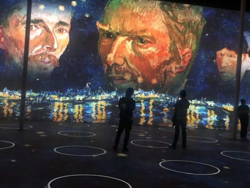 People stand in a darkened room with projections of Vincent Van Gogh on the wall.
