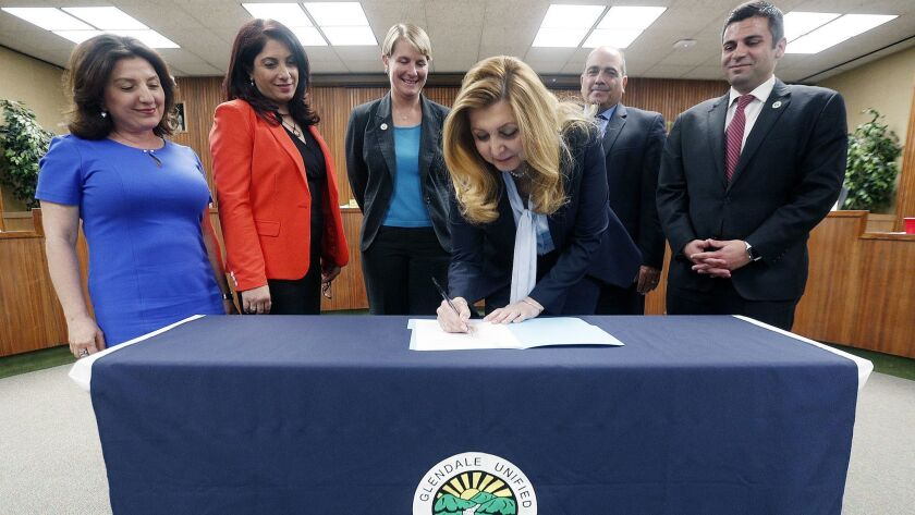 Superintendent Vivian Ekchian signs her contract with the Glendale Unified School Board behind her a