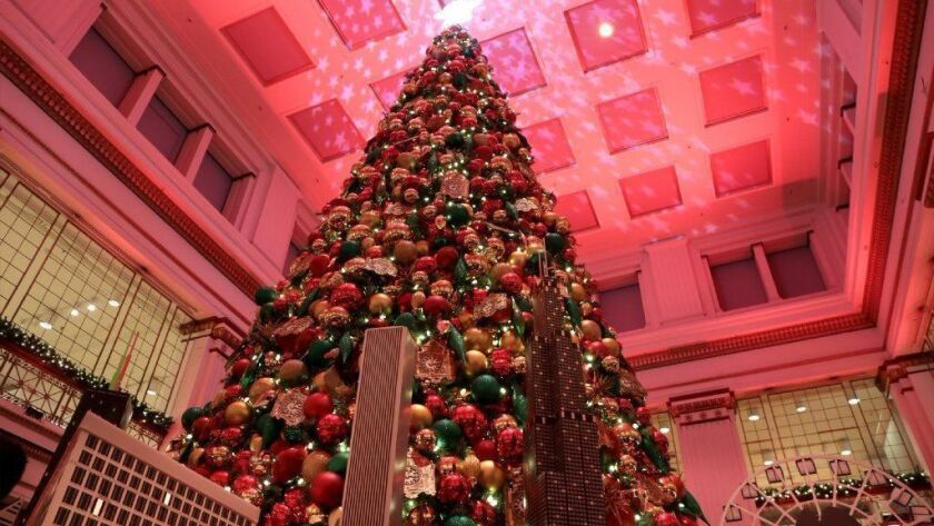 Macy's Christmas tree is displayed Nov. 13, 2018, in the Walnut Room at its State Street store in Chicago, alongside mini replicas of some Chicago landmarks.
