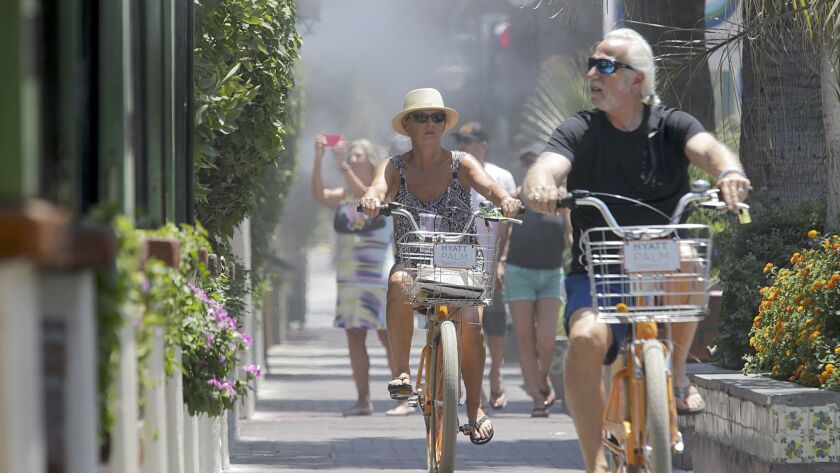 Visitors on their bikes pass under cool mist in Palm Springs on June 20, 2017, a day on which the temperature reached 122 degrees.