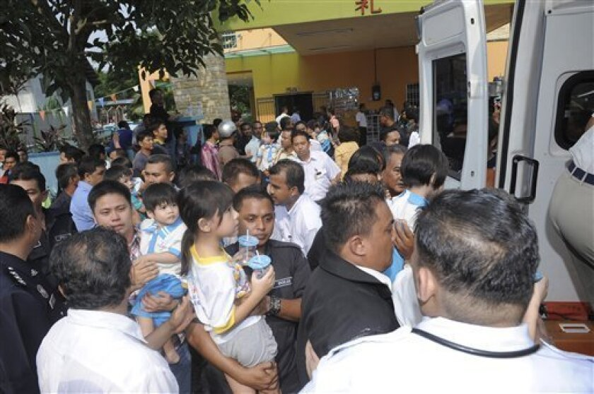 Police officers carry children who had been taken hostage to an ambulance outside a kindergarten after police rescued them in Muar, Malaysia, Thursday, July 7, 2011. Malaysian police stormed the kindergarten and subdued the hostage-taker, ending a nearly seven-hour hostage drama. (AP Photo) MALAYSIA OUT, NO SALES, NO ARCHIVE