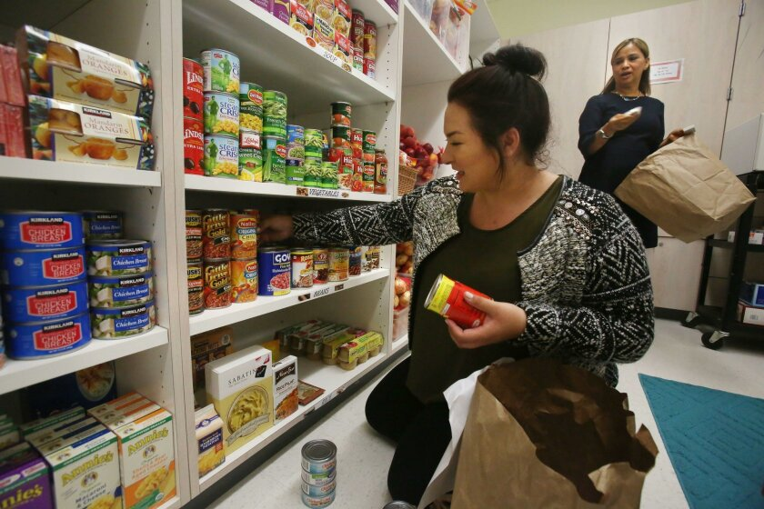 Southwestern College student Naomi Oakes stocks the shelves with canned goods as Jag Kitchen Food Pantry as director Patricia Bartow, right, asks where to put other items. An opening celebration of the pantry was held Tuesday on campus, where a survey found more than 80 percent of students said the