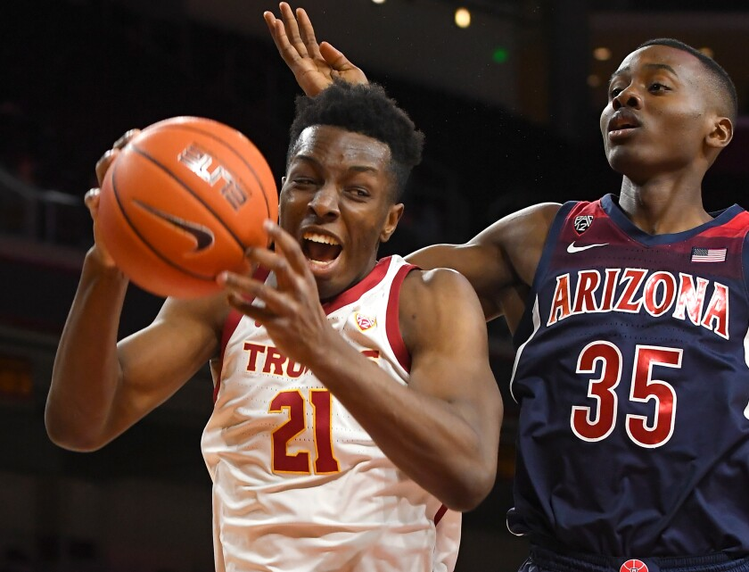 USC's Onyeka Okongwu grabs a rebound in front of Arizona's Christian Koloko during the first half of the Trojans' win at Galen Center on Thursday.