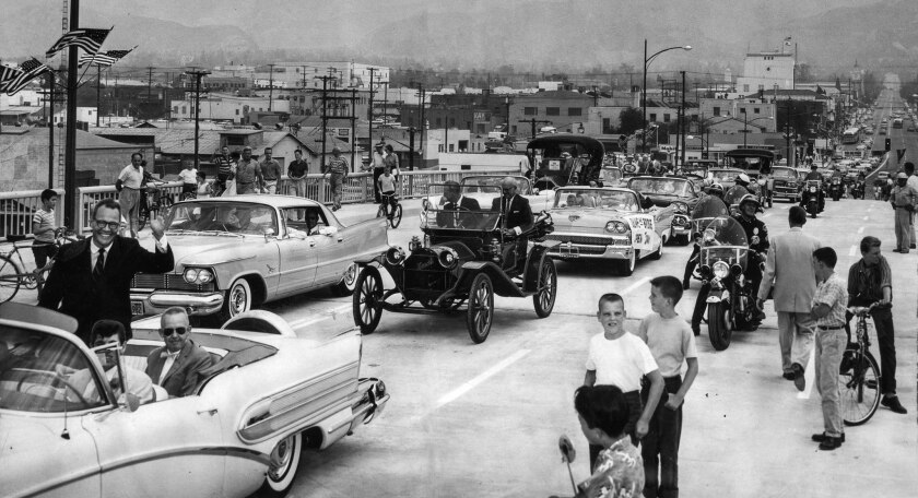 Aug. 12, 1958: Burbank Mayor Dallas Williams, left, waves from front of caravan which officially ope