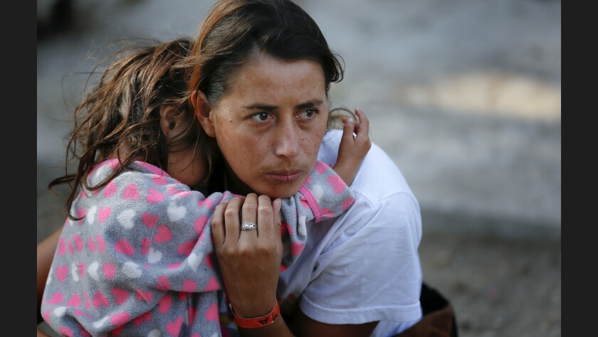 A woman and her daughter wait just outside the temporary shelter set up at Unidad Benito Juarez in Tijuana where refugees are temporary sheltered.
