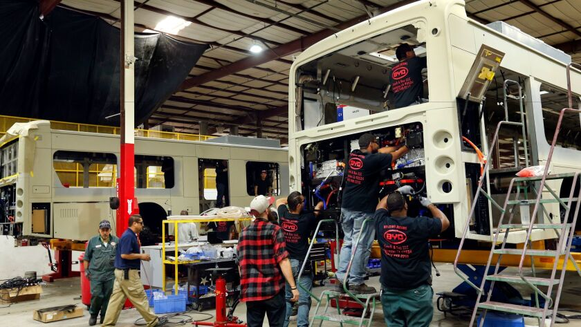 Workers install the cooling system on a 45-foot-long electric bus at BYD's manufacturing plant in Lancaster on Sept. 22, 2016.