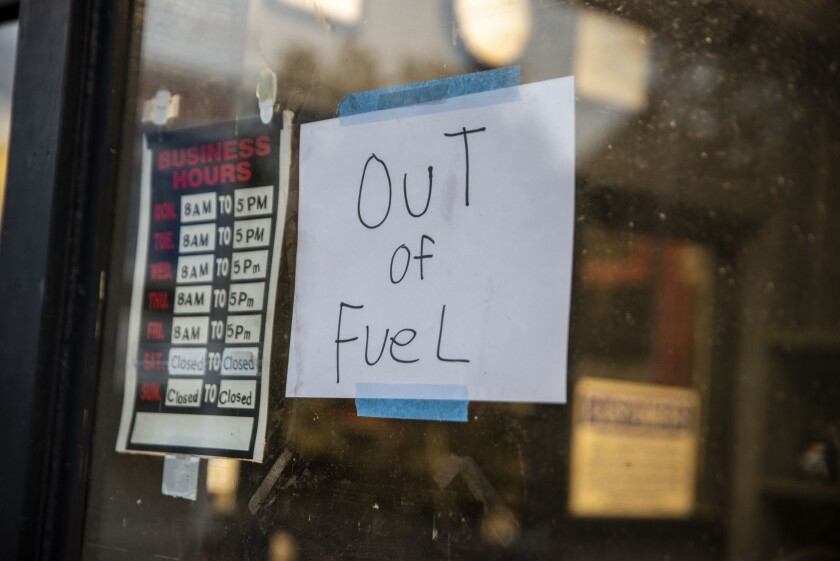 """A sign reading """"Out of Fuel"""" is taped to the window at an Exxon Gas Station."""