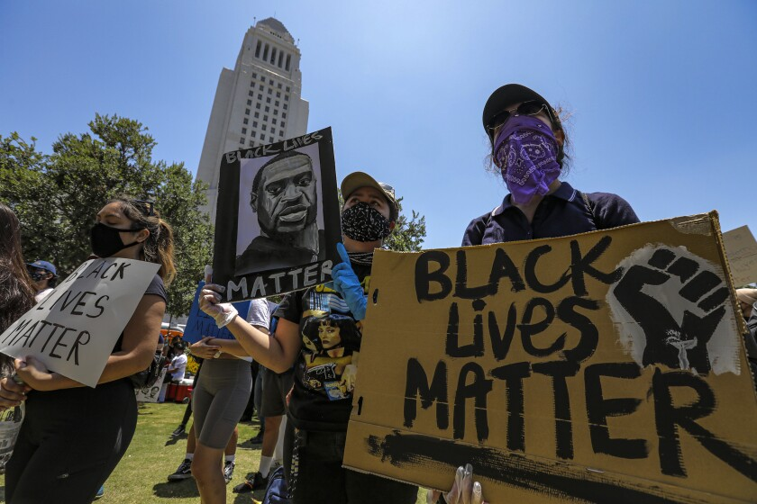 Protesters hold Black Lives Matter signs.