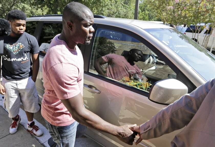 Josephus Weeks, center, nephew of Ebola patient Thomas Eric Duncan, holds hands with a family member as his son Josephus Weeks, Jr., left, looks on after the family visited their uncle at Texas Health Presbyterian Hospital Tuesday, Oct. 7, 2014, in Dallas. Texas Health Presbyterian Hospital released a statement Tuesday saying Thomas Eric Duncan is on a ventilator and is receiving kidney dialysis. The hospital says his liver function improved after declining over the weekend, but warns that his condition could vary in the coming days. (AP Photo/LM Otero)