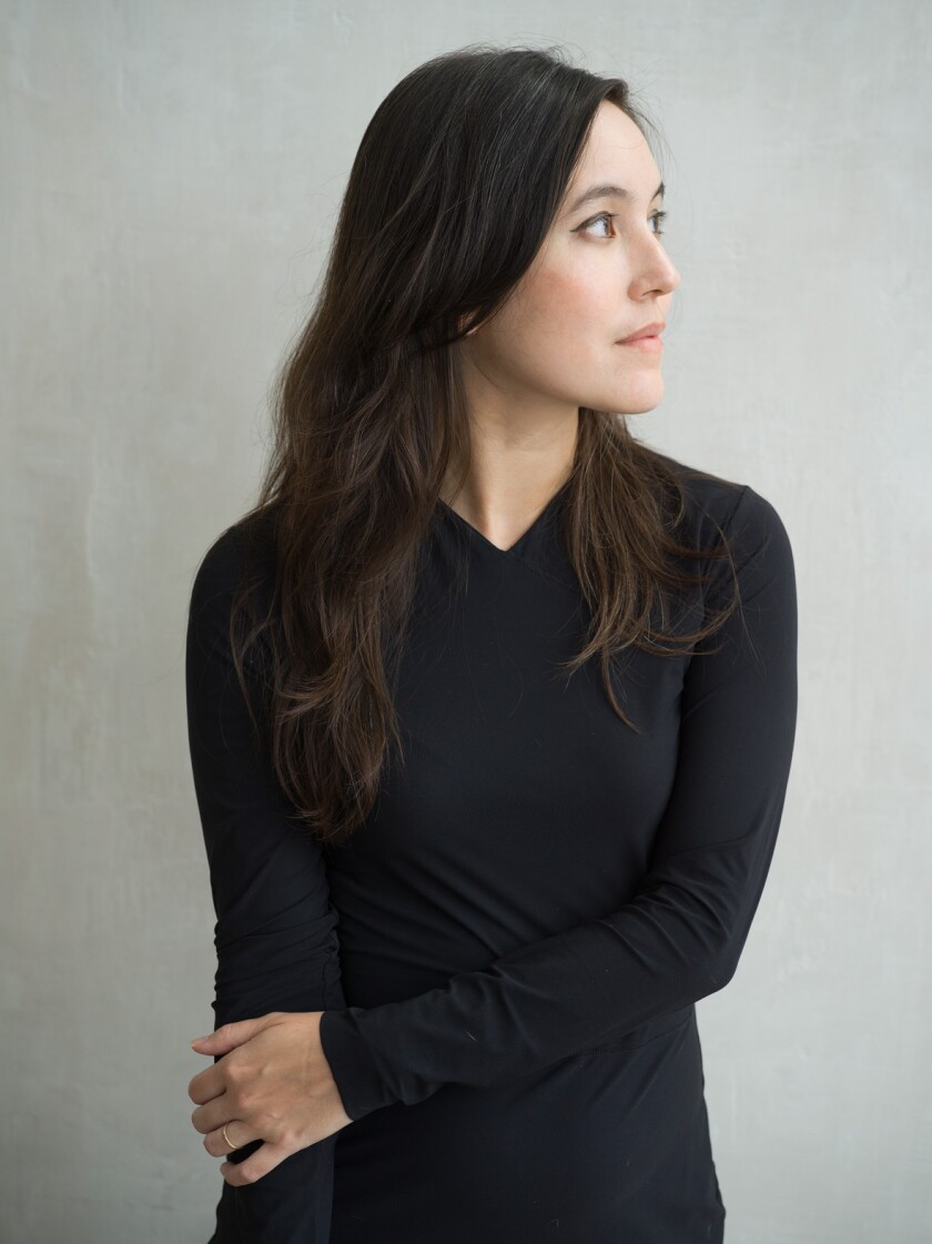 A woman in a black dress holds her right arm with her left and looks to her left