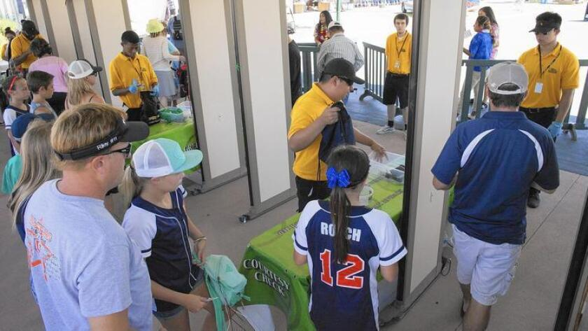 Los visitantes ingresan a través de detectores de metal en la Feria del Condado de Orange, el pasado viernes. Es el primer año en que se emplean estos dispositivos en cada entrada (Kevin Chang / Daily Pilot).