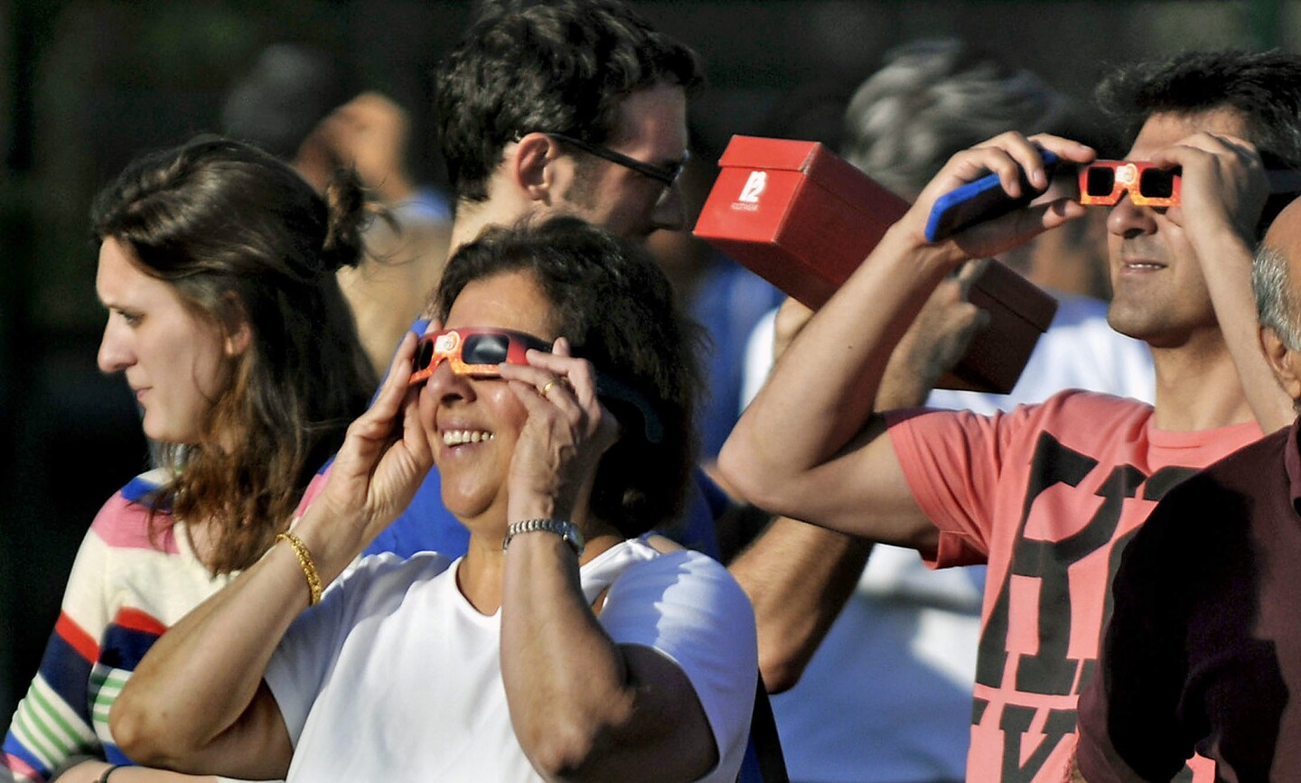 Guests use special filtered googles and pinhole boxes to look and the solar eclipse directly and indirectly.