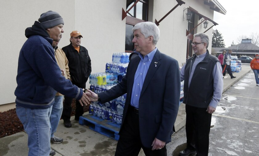 HOLD FOR STORY BY DAVID EGGERT- FILE- In a file photo from Feb. 5, 2016, Michigan Gov. Rick Snyder, center and Our Lady of Guadalupe Church Deacon Omar Odette, right, meet with volunteers helping to load vehicles with bottled water in Flint, Mich. Snyder's standing as one of the GOP's most accompli