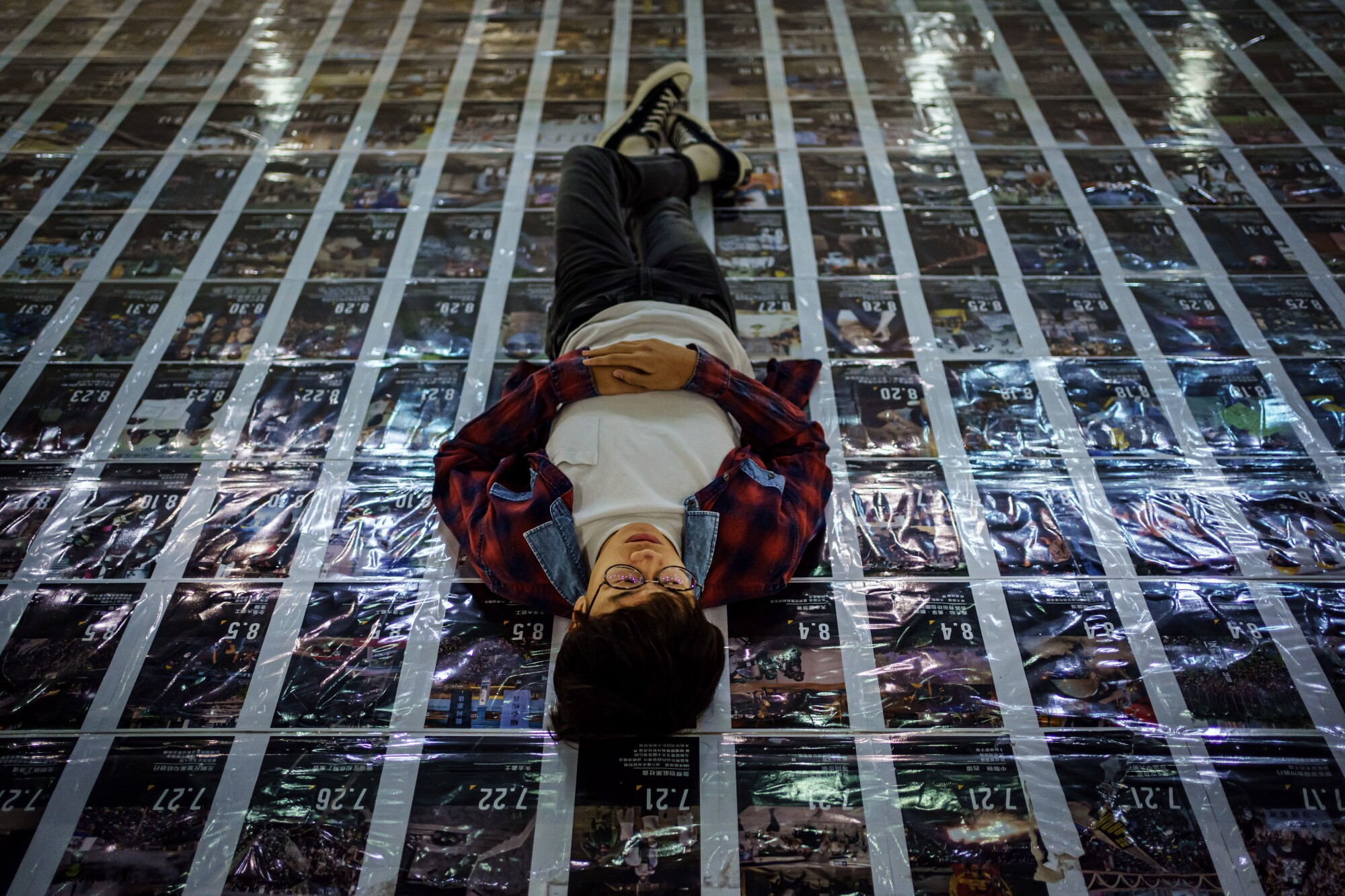 Ben Chan, a vocalist for the band Boyz Reborn, lies down on protest posters at his college.