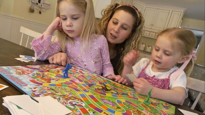 Michelle Hastings, center, plays Candy Land with her daughters Campbell Hastings, 5, left, and Peyto