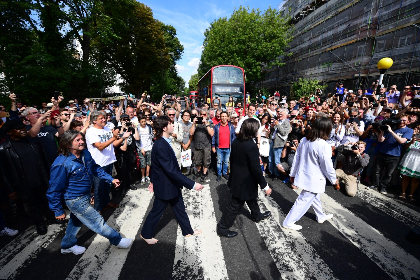 LONDON, ENGLAND - AUGUST 08: Beatles impersonators recreate the iconic 'Abbey Road' photograph made 50 years ago today, on August 8, 2019 in London, England. 50 years ago today, John Lennon, Paul McCartney, George Harrison and Ringo Starr held up traffic on the zebra crossing outside their recording studio in north London to get the cover shot for the album, Abbey Road. (Photo by Leon Neal/Getty Images) ** OUTS - ELSENT, FPG, CM - OUTS * NM, PH, VA if sourced by CT, LA or MoD **