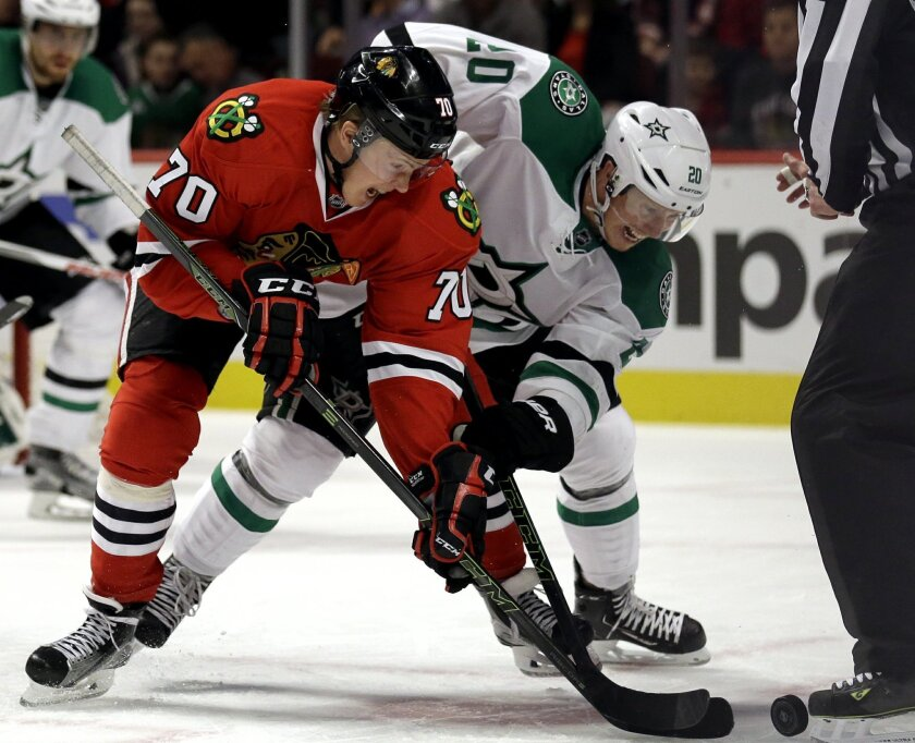 Chicago Blackhawks center Dennis Rasmussen, left, and Dallas Stars center Cody Eakin battle for the puck during the second period of an NHL hockey game Thursday, Feb. 11, 2016, in Chicago. (AP Photo/Nam Y. Huh)