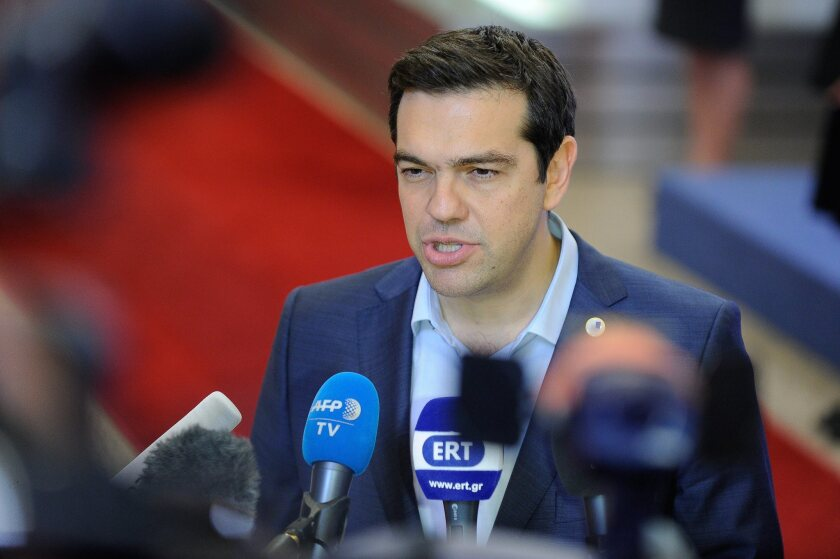 Greek Prime Minister Alexis Tsipras talks to reporters at the summit of Eurozone leaders in Brussels on July 13.