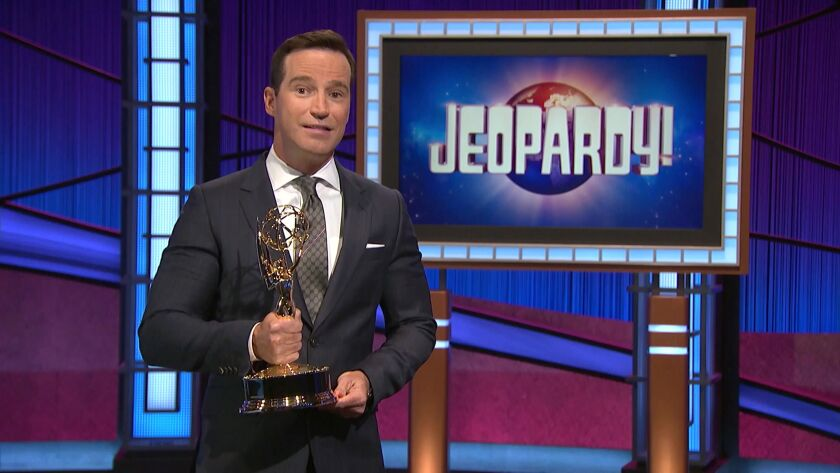 A man in a suit holding an Emmy statuette on the 'Jeopardy!' set.