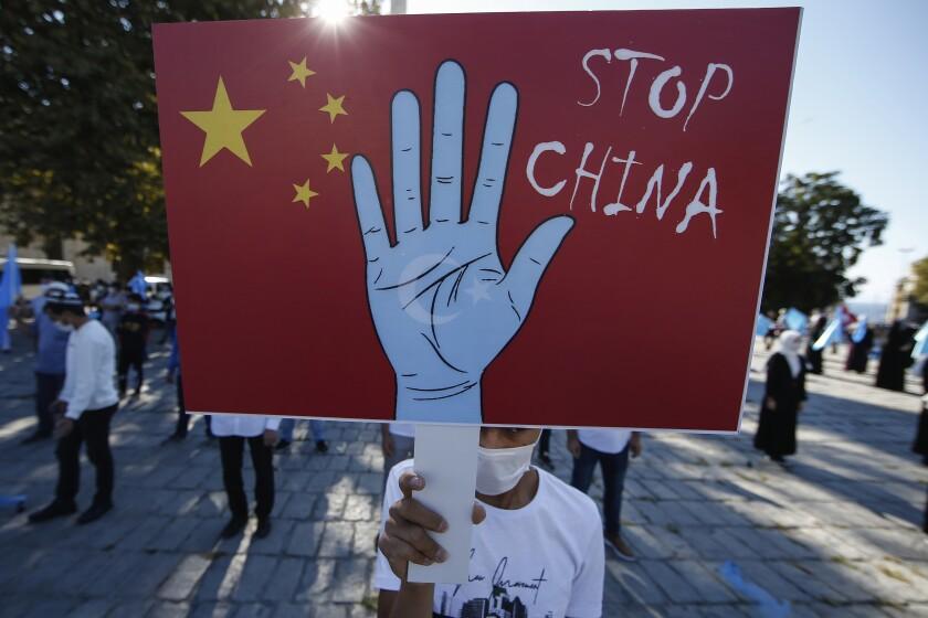 un manifestante de la comunidad uigur en Turquía sostiene una pancarta contra China