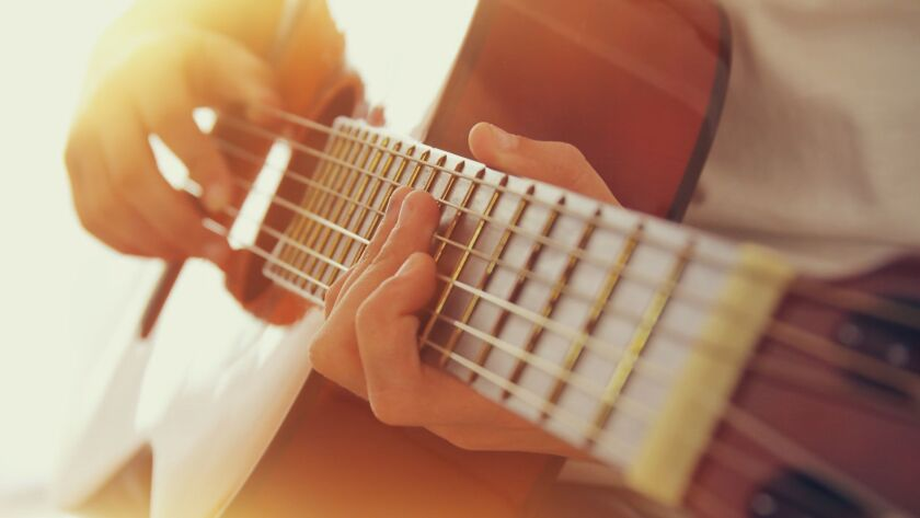 Close up of young girl playing acoustic guitar