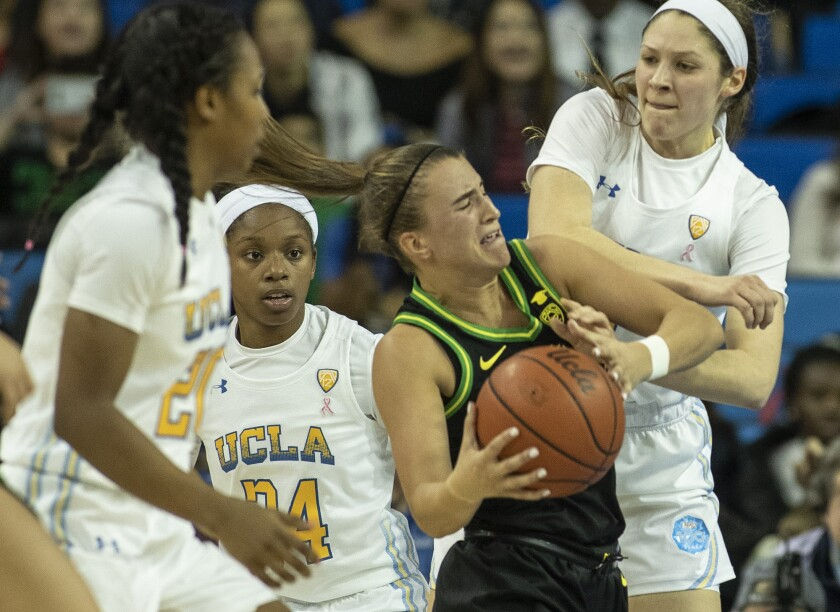 Oregon's Sabrina Ionescu is tied up by UCLA's Lindsey Corsaro, right, during the second quarter of a game Feb. 14 at Pauley Pavilion.