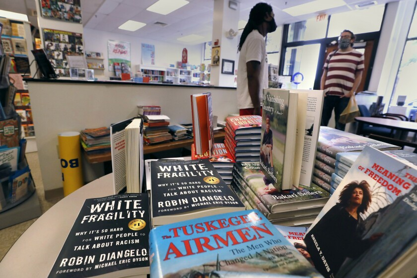 "Books are displayed, including ""The Tuskegee Airmen,"" and ""White Fragility."""
