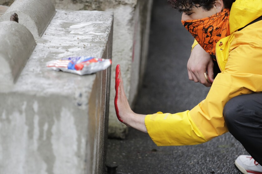 A man leaves a red paint handprint on a barricade near a closed Seattle police precinct Tuesday, June 9, 2020, in Seattle, following protests over the death of George Floyd. Floyd, a black man died after being restrained by Minneapolis police officers on May 25. Under pressure from city councilors, protesters and dozens of other elected leaders who have demanded that officers dial back their tactics, the police department on Monday removed barricades near its East Precinct building in the Capitol Hill neighborhood, where protesters and riot squads had faced off nightly. Protesters were allowed to march and demonstrate in front of the building, and the night remained peaceful. (AP Photo/Elaine Thompson)