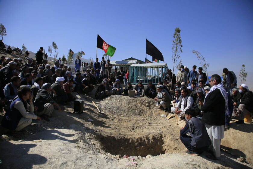 FILE - in this Oct. 25, 2020 file photo, Afghan men bury a victim of a suicide attack that targeted an education center, in Kabul Afghanistan. The U.N. says the number of civilians killed and wounded in Afghanistan fell by 15% last year, compared to 2019. A report released Tuesday, Feb.23, 2021, attributed the drop in civilian casualties in part to an apparent tactical change by insurgents to targeted killings, fewer suicide bombings, and a stark drop in casualties attributed to international military forces. (AP Photo/Mariam Zuhaib, File)