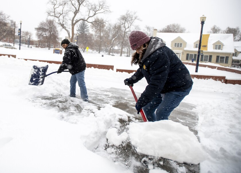 Francis Garza, Tina Longoria shovel snow at University of Northern Colorado