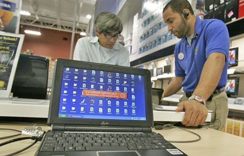 David Wells (right), an employee at Best Buy in Mission Valley, helped a customer with a netbook, a scaled-down, lower-priced laptop whose popularity boomed in 2008. (John Gibbins / Union-Tribune)