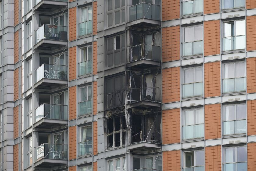 Damage to a 19-storey tower block in New Providence Wharf in London, Friday, May 7, 2021. Firefighters have tacked a blaze in a London apartment tower that has cladding similar to that used on a building where 72 people died in 2017. London Fire Brigade said about 125 firefighters tackled a fire on Friday that spread to three floors of a 19-story building in the city's docklands. (Yui Mok/PA via AP)