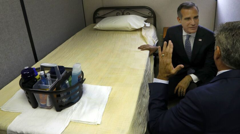 Los Angeles Mayor Eric Garcetti, left, and Executive Director of The People Concern John Maceri, right, at a temporary shelter trailer facility in El Pueblo in Los Angeles on Sept. 5.