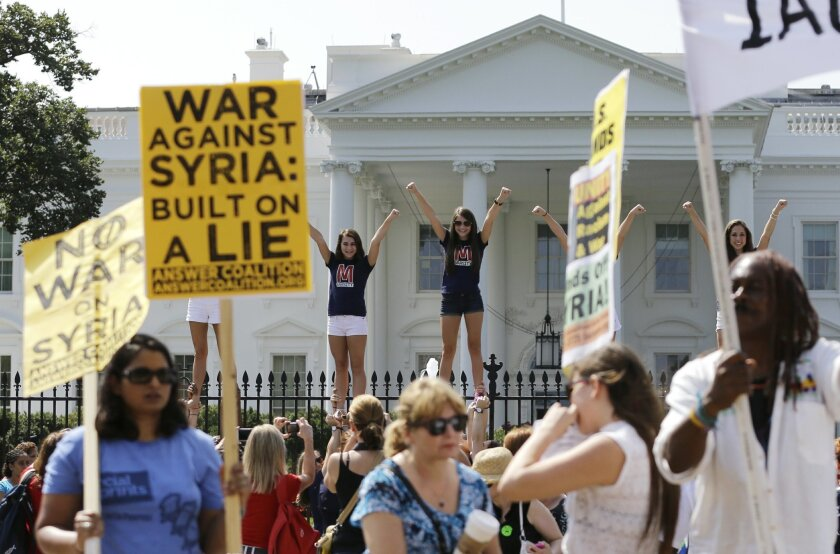 As members of the Answer Coalition set up to protest against military action in Syria a group of cheerleaders girls pose for photos in front of the White House on Saturday, Aug. 31, 2013, in Washington.