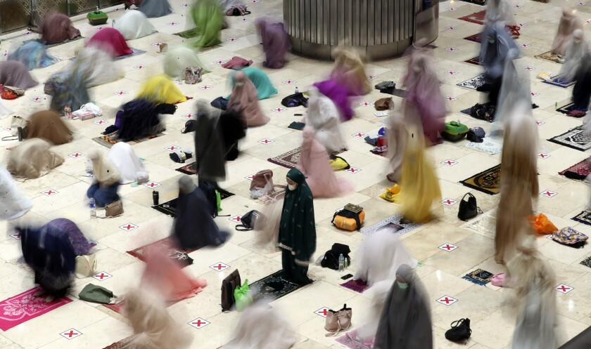 """In this photo taken using slow shutter speed, Muslim women offer an evening prayer called """"tarawih"""" marking the first eve of the holy fasting month of Ramadan at Istiqlal Mosque in Jakarta, Indonesia. Monday, April 12, 2021. During Ramadan, the holiest month in Islamic calendar, Muslims refrain from eating, drinking, smoking and sex from dawn to dusk. (AP Photo/ Achmad Ibrahim)"""