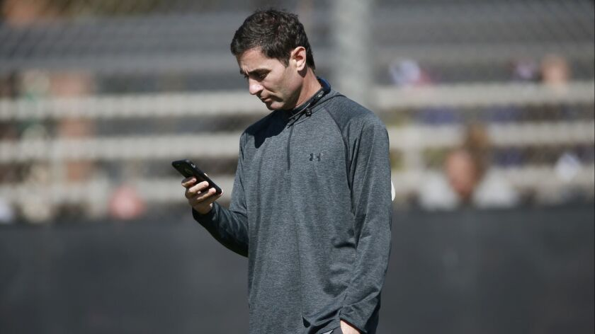 Padres Gereral Manager A.J. Preller looks at his phone during a spring training workout on Tuesday.