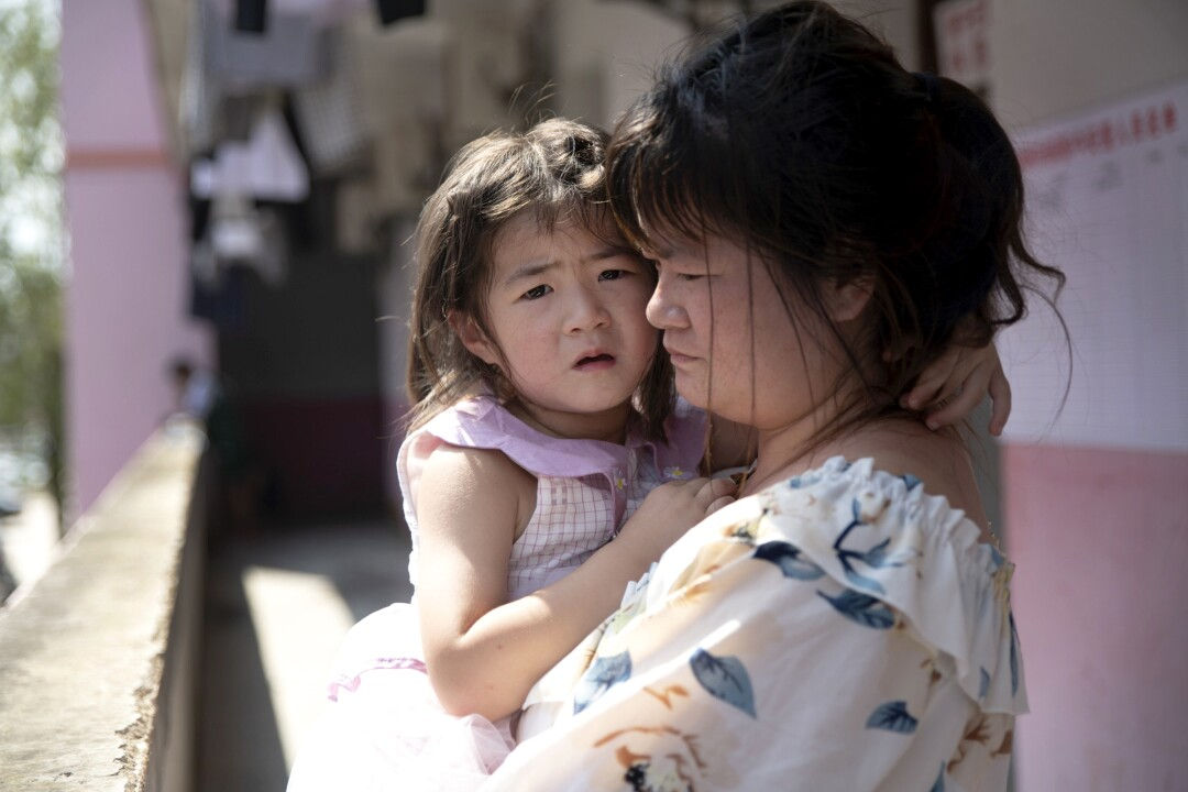 Mrs. Huang holds her daughter Huang Minfang, who is afraid of the floods.