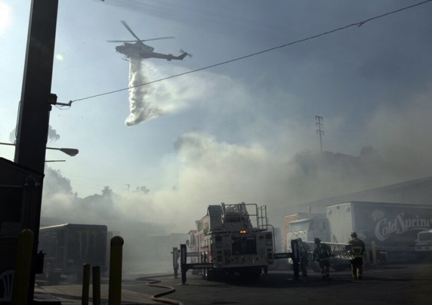 Helicopters made water drops to dampen the flames and firefighters were quick to protect the houses on the surrounding ridge above a  fire at a  beverage  distributor on Delevan Drive near 34th Street.